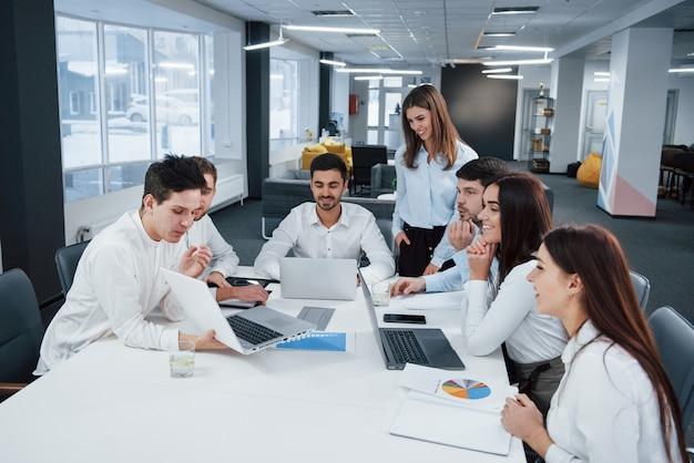 Mostra buoni risultati. il gruppo di giovani liberi professionisti nell'ufficio ha conversazione e sorridere