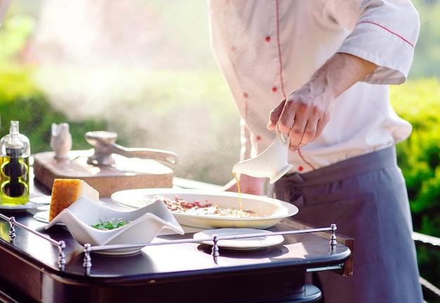 Mostra cucina. il cuoco prepara la famiglia carpaccio per gli ospiti del ristorante.
