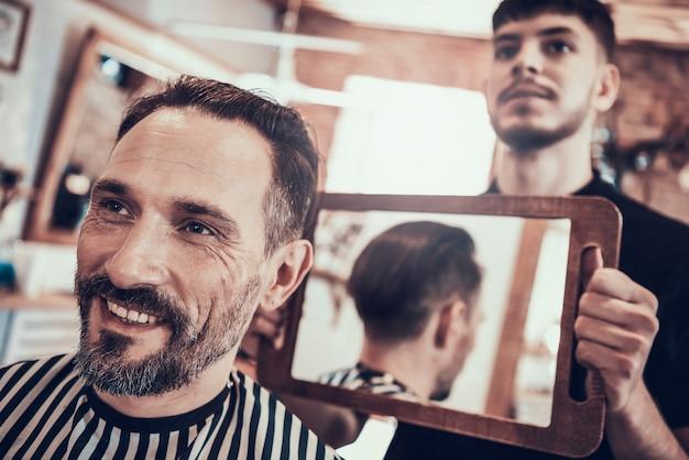 Mostra di barbiere a specchio taglio di capelli al cliente