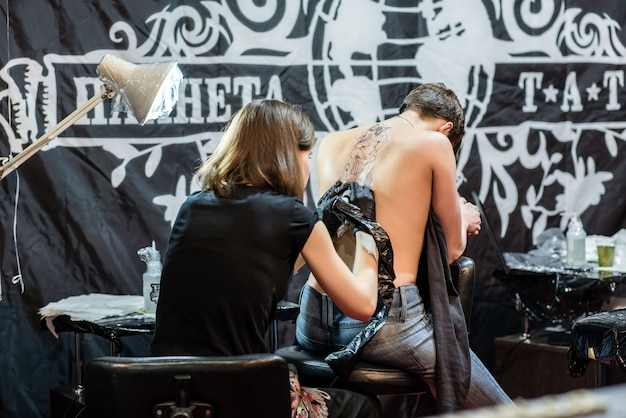 Mostra il processo di fare un tatuaggio da artista di ragazza professionista in studio