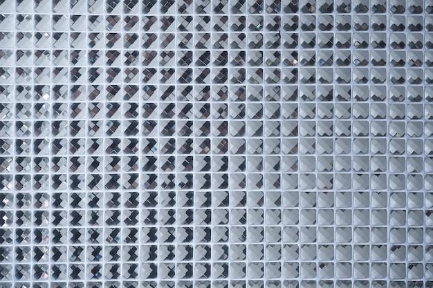 Motivo a mosaico in argento di piastrelle. la parete è decorata con un piccolo piatto in vetro colorato, un bellissimo muro a mosaico o un muro in ceramica per lo sfondo del modello