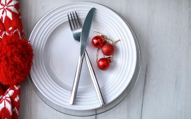 Motivo di sfondo di natale di piatti cucchiai e forchette e sciarpa rossa