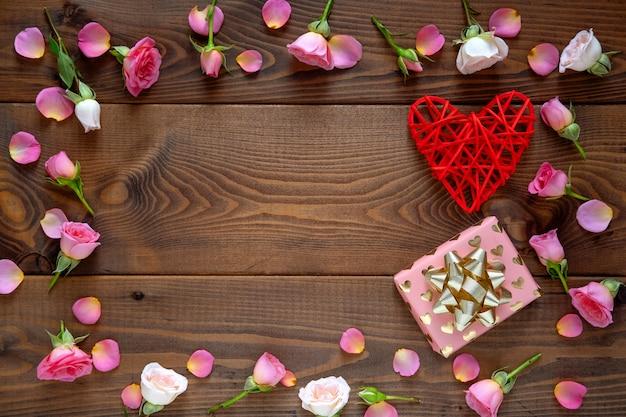 Motivo floreale fatto di rose rosa e beige, foglie verdi su fondo in legno. sfondo di san valentino.