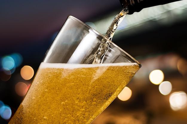 Moto di birra versando dalla bottiglia in vetro