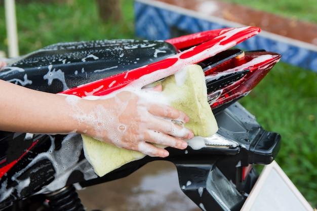 Moto pulita, mano femminile con spugna schiuma gialla lavaggio di una moto.