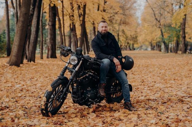 Motociclista barbuto pone sulla propria moto, detiene il casco, cavalca una moto, pone all'aperto nel parco