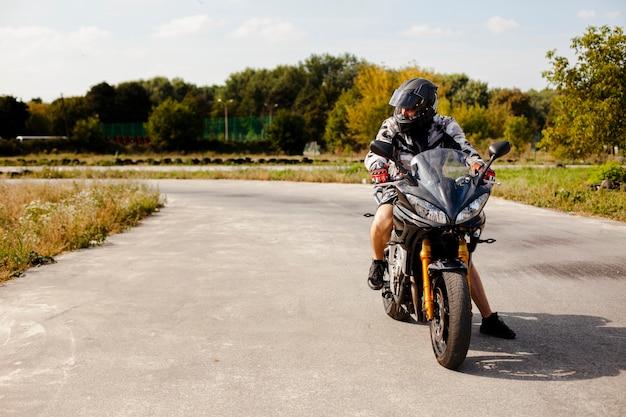 Motociclista che guida con attenzione sulla strada