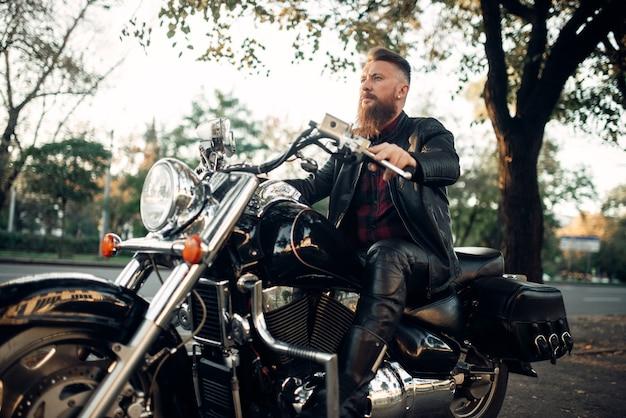 Motociclista che si siede su una moto che si appoggia su un casco