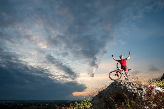 Motociclista cross country che si rilassa sulla cima della montagna