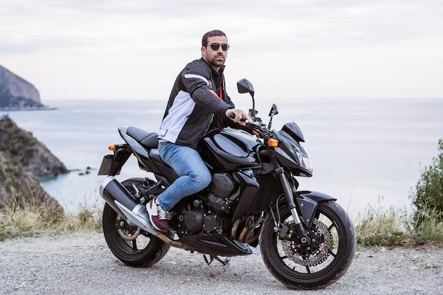 Motociclista del giovane con la sua motocicletta nera pronta a guidare, di fronte al mare