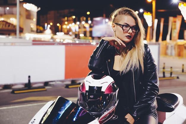 Motociclista della donna del ritratto che gode della vita di città di notte che si siede sulla motocicletta