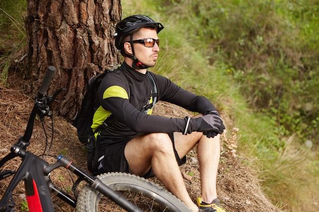 Motociclista di montagna maschio che riposa sul viaggio in bicicletta, seduto a terra sotto agli alberi con la sua bicicletta elettrica