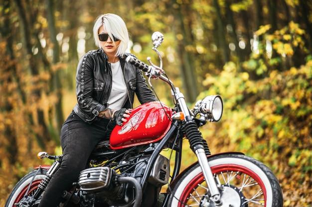 Motociclista femminile abbastanza biondo con una motocicletta rossa