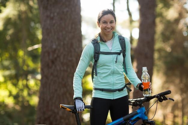 Motociclista femminile che sta con il mountain bike in foresta