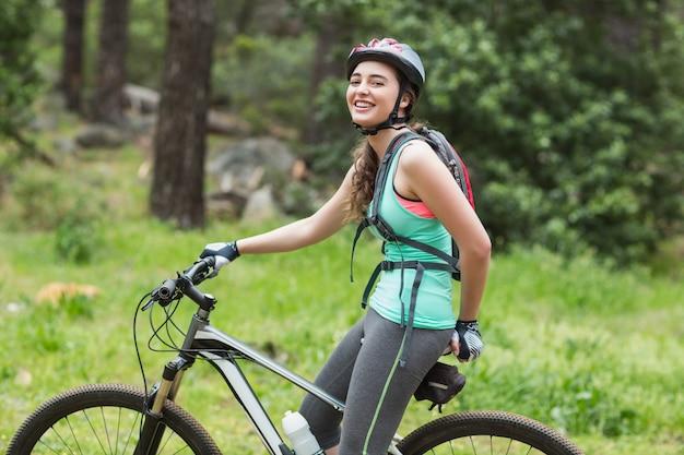 Motociclista femminile felice in foresta