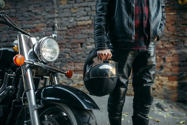 Motociclista in giacca di pelle con casco in mano vicino all'elicottero classico.
