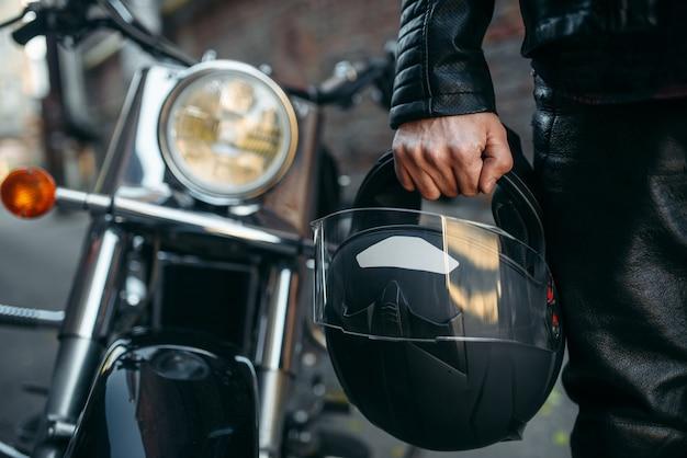 Motociclista in giacca di pelle con casco in mano