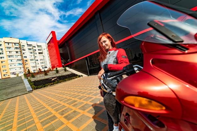 Motociclista in piedi vicino a una moto guardando la telecamera con casco in mano