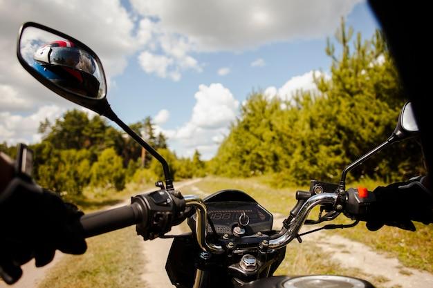 Motociclista in sella a moto su strada sterrata