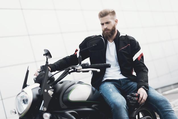Motociclista maschio brutale che si siede sul motociclo