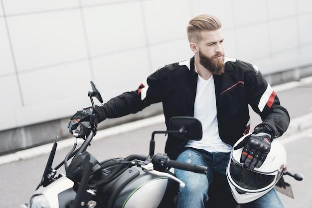 Motociclista maschio brutale del collage che si siede sulla motocicletta