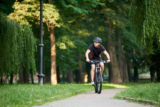 Motociclista maschio tonificato che guida la bici giù il vicolo del parco il giorno di estate