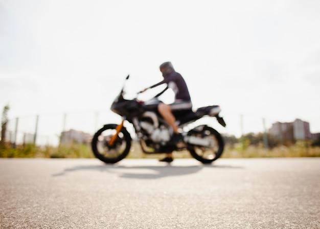 Motociclista offuscata parcheggiato sulla strada