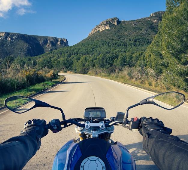 Motociclista su una splendida strada diurna