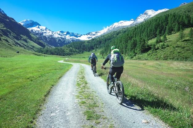 Motociclisti sulla strada sterrata di montagna nel bellissimo paesaggio delle montagne