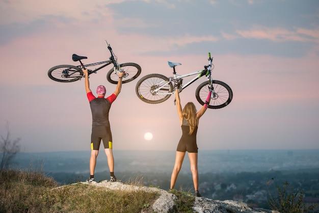 Motociclisti uomo e donna che tengono le bici in alto
