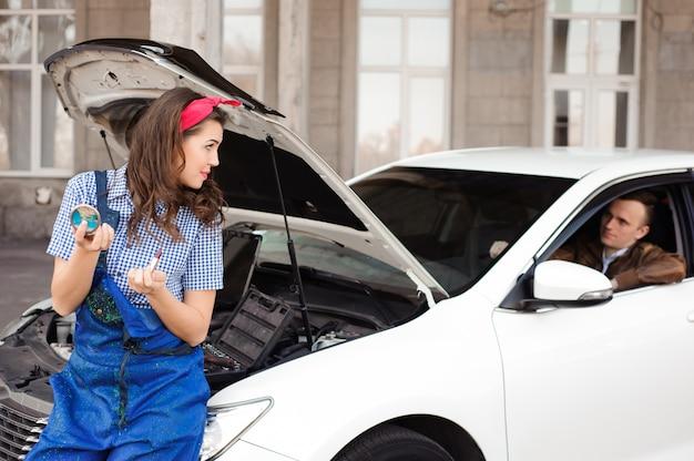Motore di automobile d'esame della ragazza attraente sveglia alla riparazione automatica