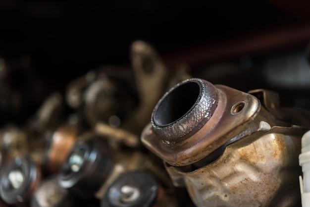 Motore e marmitta di automobile smontati al garage