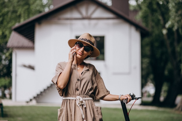 Motorino di guida della giovane donna e parlare sul telefono in parco