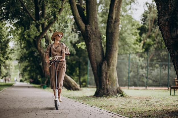 Motorino di guida della giovane donna in parco
