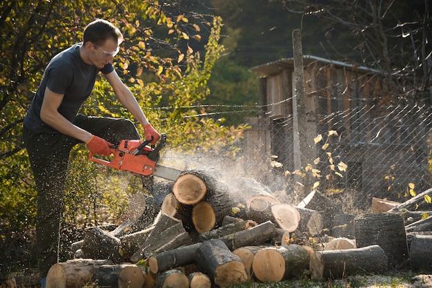 Motosega che si trova su un mucchio di legna da ardere nel cortile