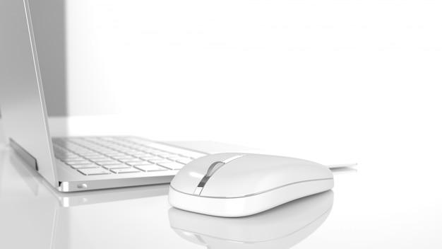 Mouse accanto al computer portatile sul banco di lavoro di messa a fuoco selettiva su sfondo bianco.