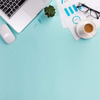 Mouse, computer portatile, pianta del cactus, occhiali, piano del preventivo e tazza di caffè su priorità bassa blu