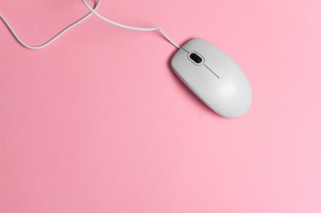 Mouse del computer con un cavo su una carta rosa