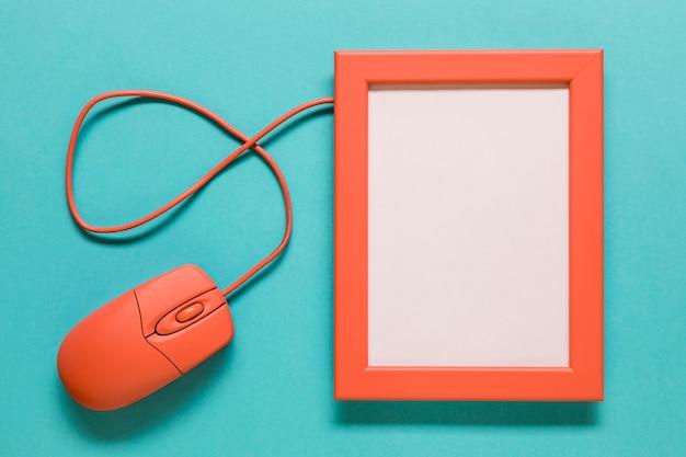 Mouse del computer e cornice vuota su sfondo blu