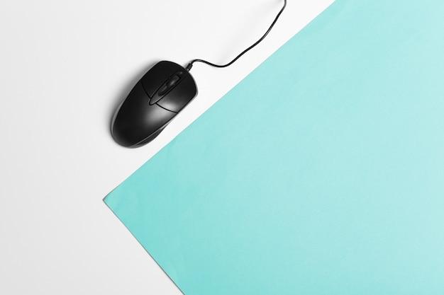 Mouse del computer su uno sfondo di carta turchese