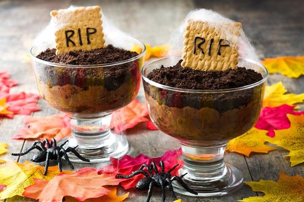 Mousse al cioccolato di halloween con biscotto tomba sulla tavola di legno