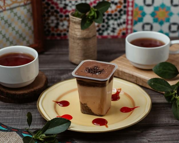 Mousse di crema al cioccolato in una tazza con due tazze di tè nero