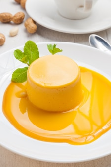 Mousse molto tenera di olivello spinoso su un piatto bianco decorato con menta