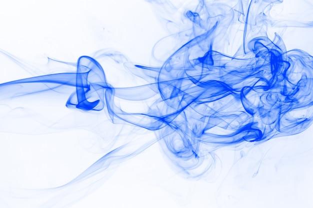 Movimento del fumo blu su sfondo bianco, colore dell'acqua dell'inchiostro