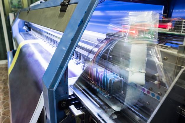 Movimento della testa di stampa a getto d'inchiostro lavorando su banner blu