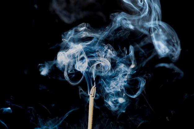 Movimento di fumo dal bastoncino d'incenso su fondo nero