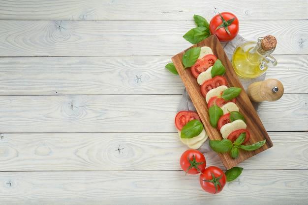 Mozzarella e pomodoro con foglie di basilico su un fondo di legno bianco