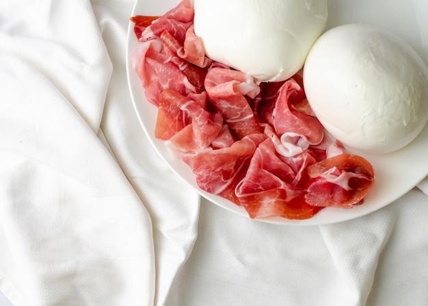 Mozzarella e prosciutto crudo sul piatto bianco.