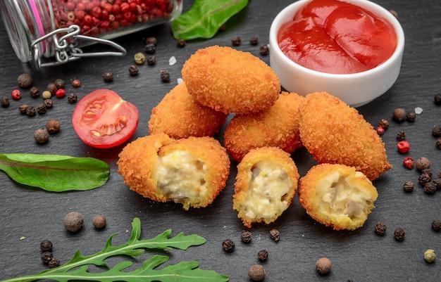 Mozzarella fritta, morsi di formaggio cheddar, palline con ketchup su tavola di pietra rustica