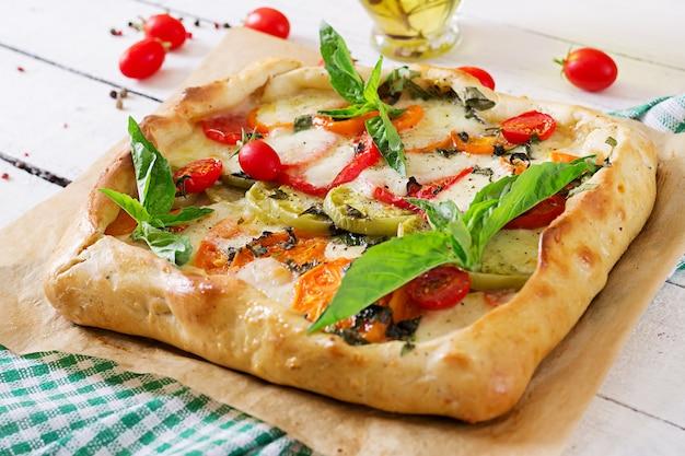 Mozzarella, pomodori, torta salata al basilico su una tavola di legno bianca. cibo delizioso, antipasto in stile mediterraneo.